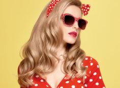 Портретное фото на аву гламурной девушки со светлыми волосами с бантом, в солнечных очках и красном платье в горошек.
