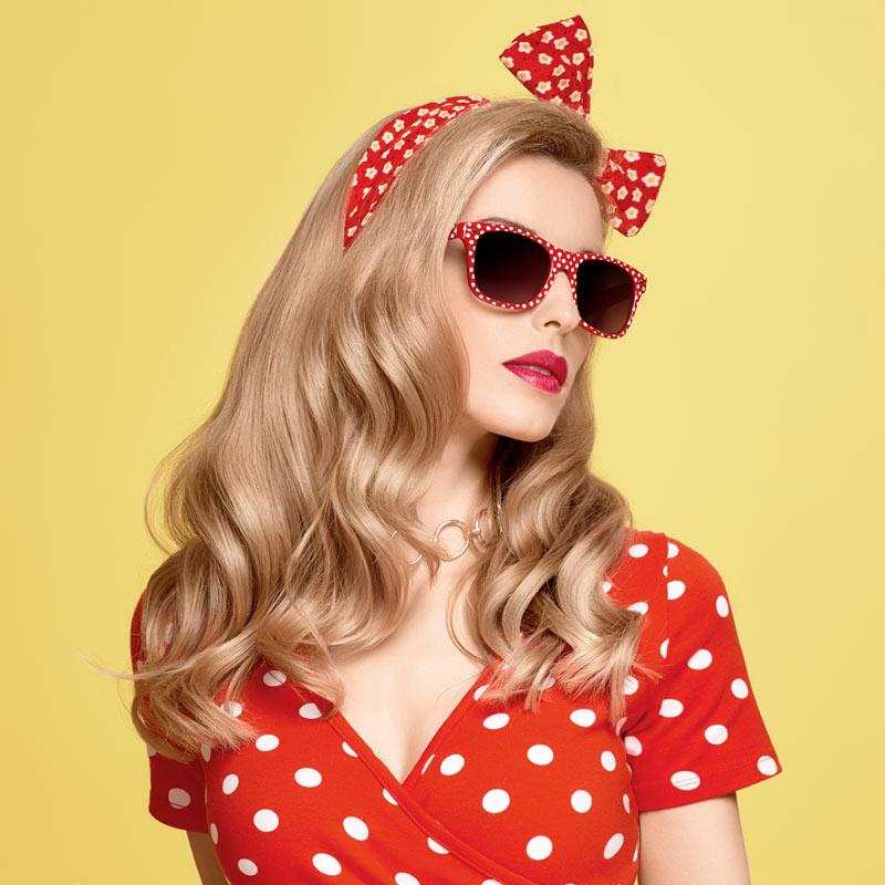 Портретное фото гламурной девушки в красном платье в горошек.