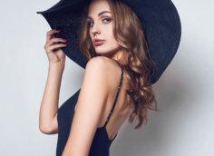 Фото на аву красивой девушки с длинными волосами в черной шляпе и платье с открытыми плечами.