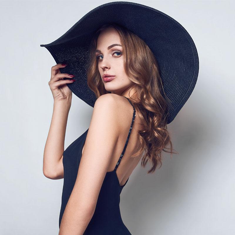 Фото красивой девушки с длинными волосами в черной шляпе и платье с открытыми плечами.