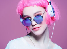 Потретная фотография на аву девушка с розовыми волосами, в солнечных очках и наушниках.