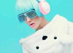 Яркое фото девушки с голубыми волосами, в солнечных очках и наушниках на лазурном фоне.
