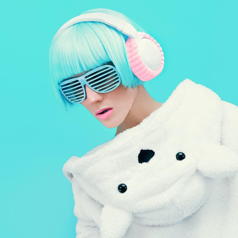 Яркое фото девушки с голубыми волосами, в солнечных очках и наушниках.