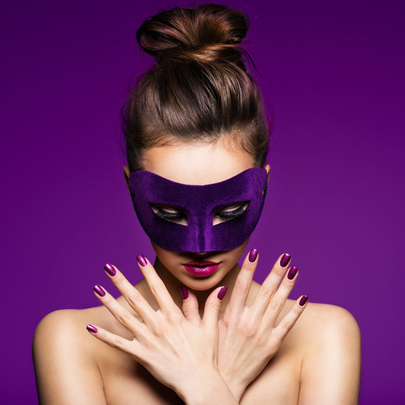 Фото на аву девушка в фиолетовой маскарадной маске со скрещенными на груди руками на пурпурном фоне.