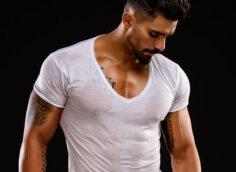 Фото парня с черными волосами и бородой в мокрой футболке белого цвета.