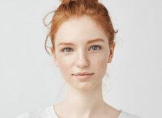 Портретное фото рыжей девушки на аву в светлой футболке на белом фоне.