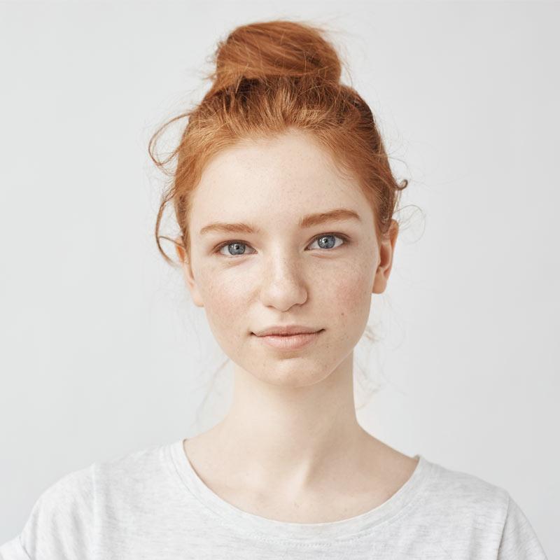 Портретное фото рыжей девушки в светлой футболке на белом фоне.