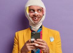 Прикольное фото на аватарку мужчина в жёлтом пиджаке и галстуке, с перевязанной головой и телефоном в руках.